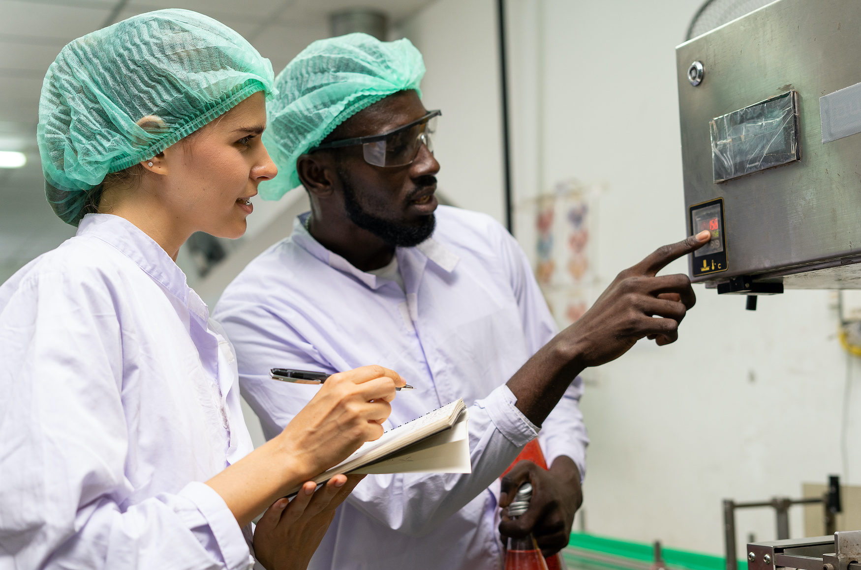 A quality supervisor or food technician explains the use of the Shrink Tunnel Machine to the new employee. Quality inspectors work together in the food factory to inspect food quality in standards.